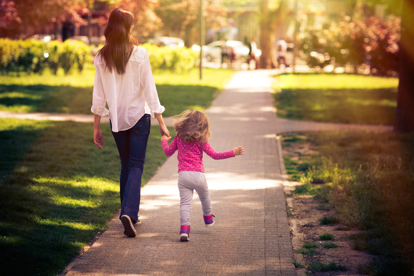 Mother And Daughter Taking A Walk In The Park